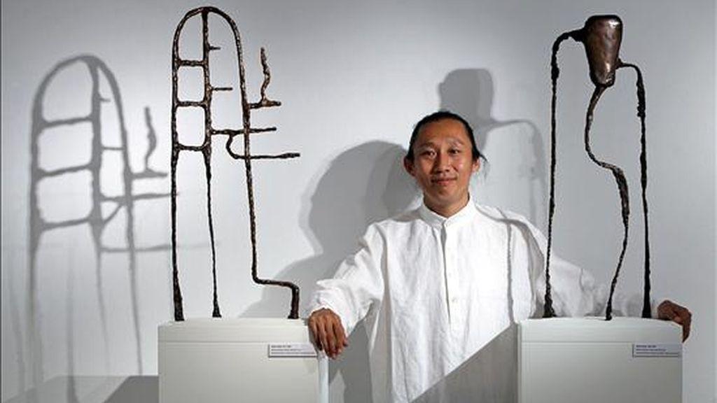 El artista chino Wang Xieda posa entre sus obras, Sages's Saying 013, y Sages's Saying 058. EFE