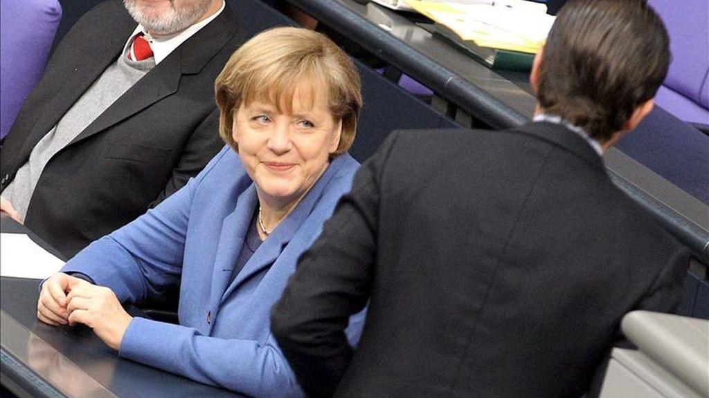 La canciller alemana, Angela Merkel, sonríe al ministro de Defensa Karl-Theodor zu Guttenberg, durante un debate en el Bundestag (Parlamento alemán). EFE/Archivo