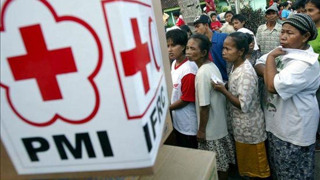Supervivientes indonesios del terremoto de junio de 2006 hacen fila para recibir comida donada por la Agencia para el Desarrollo Internacional de Estados Unidos (USAID) y la Cruz Roja Internacional en Bantul (Indonesia). Las autoridades indonesias han expulsado a la Cruz Roja Internacional de las regiones de Papúa y Aceh. EFE/Archivo