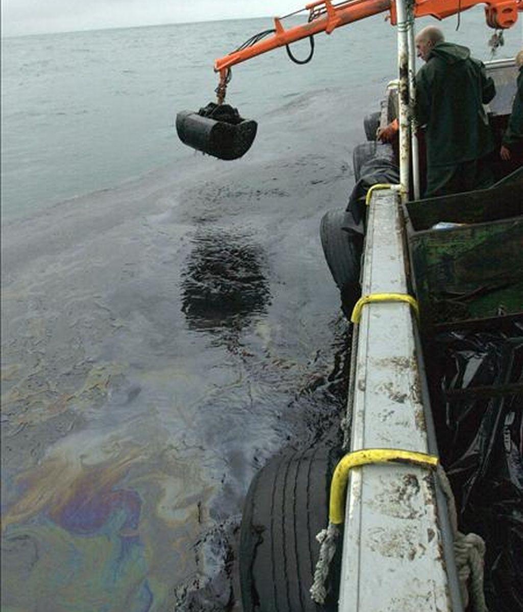 Marineros de la ría de Arosa recogen el petróleo del mar con la grúa de su barco pesquero durante la movilización para evitar que la mancha de fuel entre en la ría, tras el accidente del Prestige. EFE/Archivo