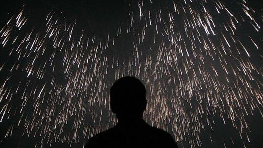 """Un hombre contempla el lanzamiento de """"La Palmera Imperial"""", durante el espectáculo de pirotécnia en la Nit De L'Albá de las fiestas de Elche (Alicante). EFE/Archivo"""