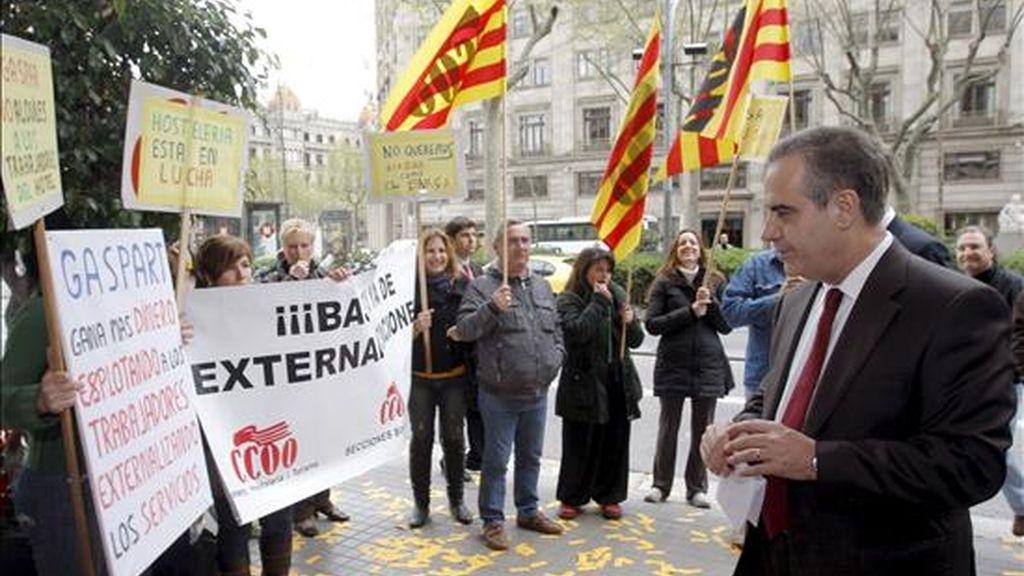 """El ministro de Trabajo e Inmigración, Celestino Corbacho (d) junto a unos trabajadores que realizan una protesta contra la externalización en HUSA ante un hotel de la cadena en Barcelona, donde el ministro protagonizó la conferencia-coloquio """"Recuperación económica y empleo"""", organizada por el foro Tribuna Barcelona. EFE"""