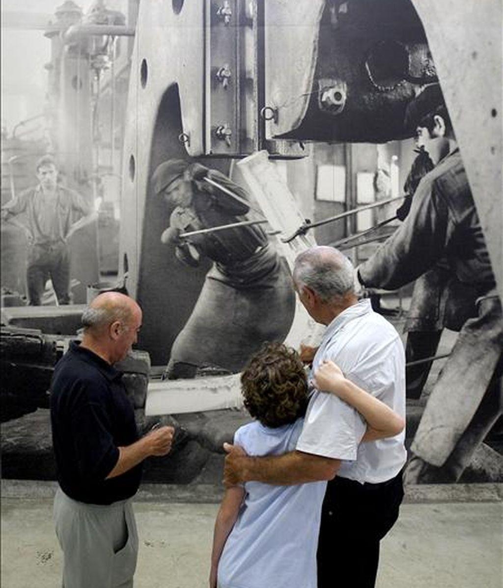Dos vecinos de Legazpi (Guipuzcoa) muestran a un niño una de las fotografías de Catalá Roca expuestas en el Chillida Lantoki, un nuevo museo ubicado en una antigua empresa papelera que refleja la relación del arte del escultor vasco Eduardo Chillida con la industria, particularmente con la gran forja de Patricio Echeverria. EFE