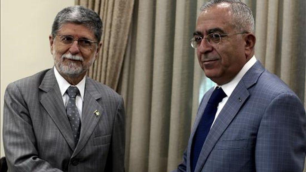 El primer ministro palestino, Salam Fayyad (d), posa junto al ministro de Exteriores brasileño, Celso Amorim, antes de su reunión hoy en Ramala (Cisjordania). EFE