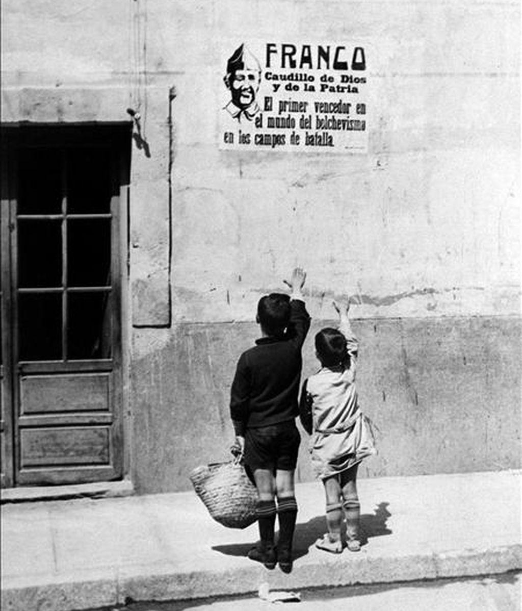 Carteles de Franco en los pueblos españoles al terminar la Guerra Civil. Dos niños alzan los brazos, en saludo fascista, a un cartel con la foto de Franco. EFE/Archivo