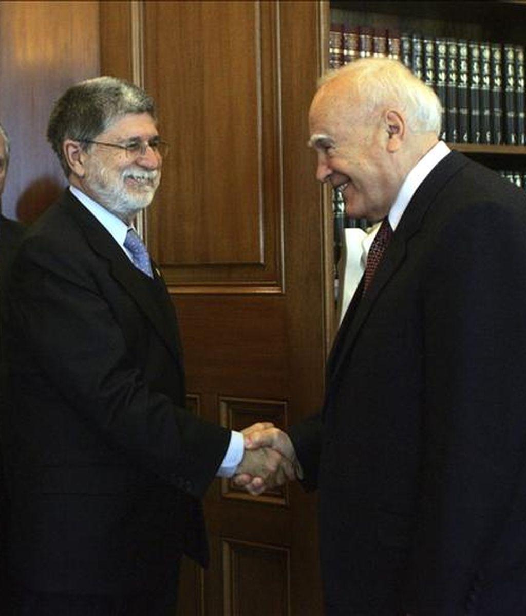 El presidente griego, Karolos Papoulias (dcha), estrecha la mano del ministro de Asuntos Exteriores de Brasil, Celso Amorim (izq), durante su encuentro en Atenas, Grecia, el pasado viernes, 3 de abril. EFE