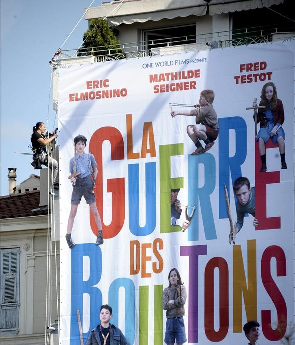 """Varios operarios despliegan un enorme cartel publicitario de la cinta """"La Guerre de boutons"""" (1962), del fallecido actor, director y productor de cine francés Yves Robert, que se presentará en el Marché du Film del Festival de Cannes (Francia), hoy, lunes 09 de mayo de 2011. EFE"""