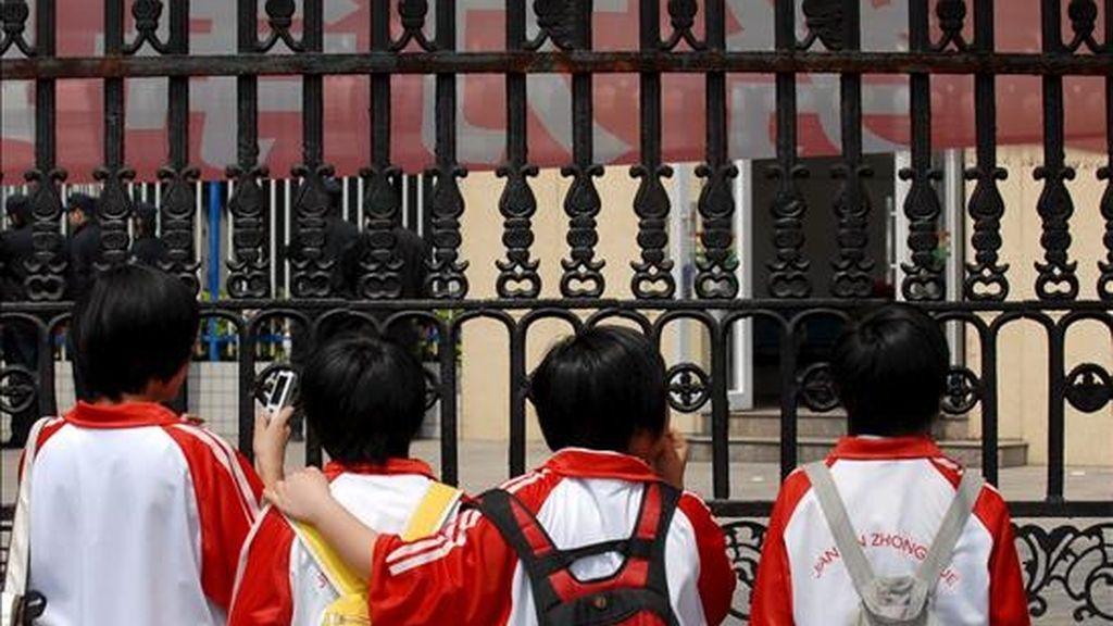 Niños observan tras las rejas de una escuela donde un hombre atacó a varios niños con un arma blanca, en Nanping, al este de China, el pasado mes de marzo. EFE/Archivo