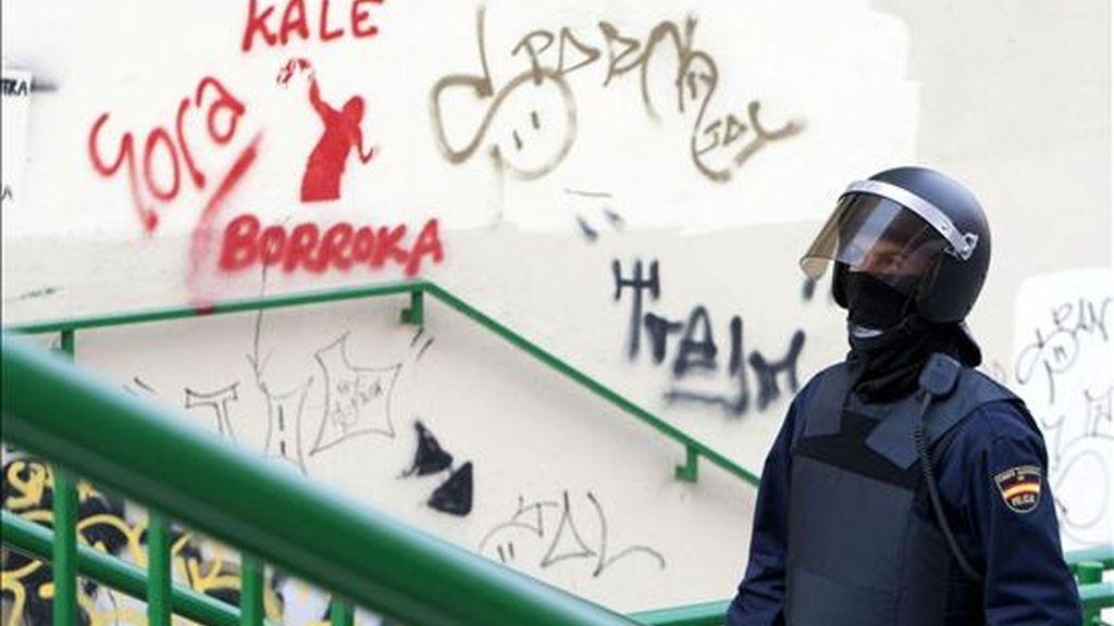 """Un agente del Cuerpo Nacional de Policía pasa junto a una pintada en la que se lee """"Viva la lucha callejera"""". EFE/Archivo"""