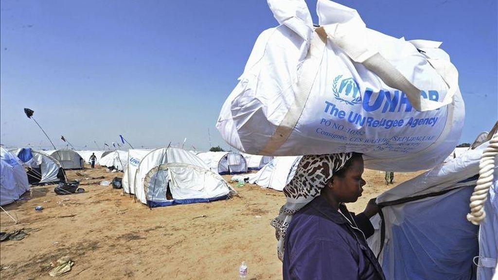 Una refugiada carga ayuda humanitaria en su cabeza, en el campo de refugiados de ACNUR, en el paso de Ras el Jedir, por donde han salido más de 100.000 refugiados del conflicto libio. EFE/Archivo
