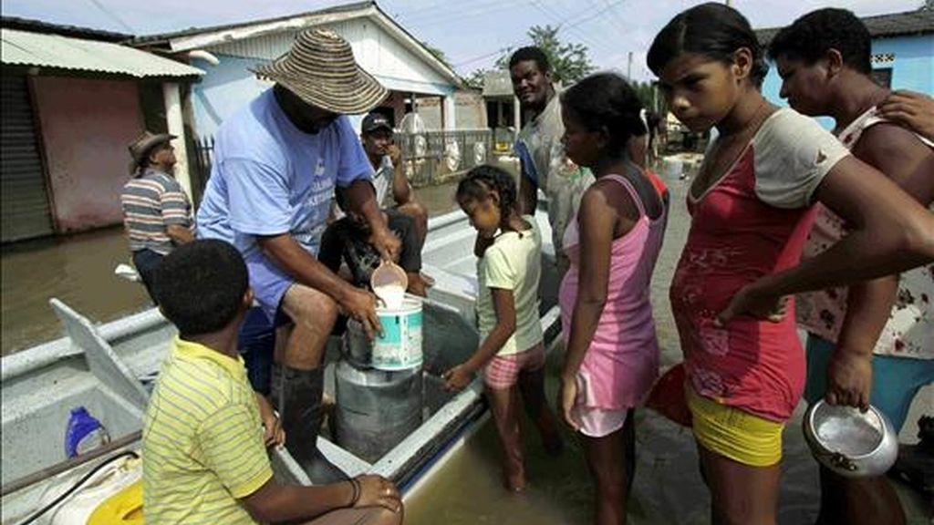 Un hombre reparte leche en la población de Pedraza, norte de Colombia. Miles de habitantes de este municipio viven en cambuches para huir de la inundación que cubrió este pequeño poblado el pasado 26 de noviembre. EFE