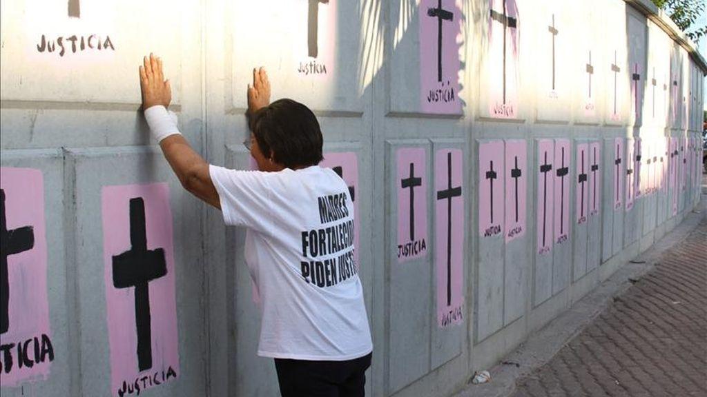 Una mujer pinta cruces en Ciudad Juarez, en homenaje a las mujeres asesinadas en la zona. EFE/Archivo