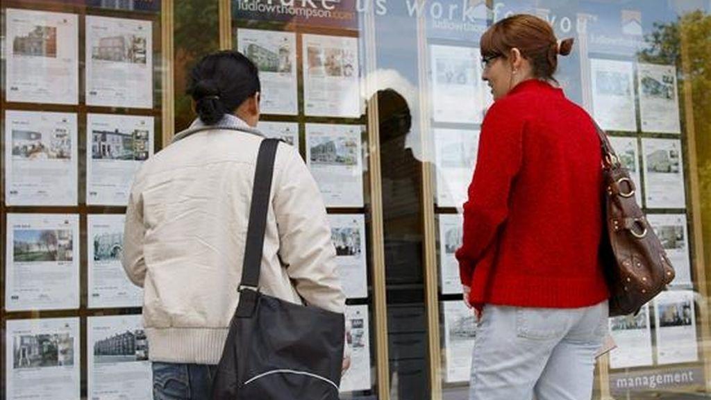 Dos mujeres leen detenidamente un escaparate con carteles de viviendas en venta. EFE/Archivo
