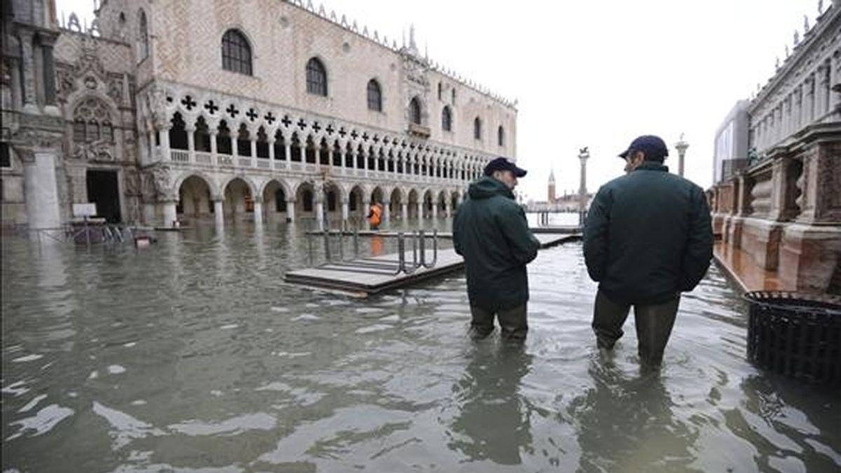 Turistas caminan hoy por la inundada plaza de San Marcos en Venecia en Italia. El nivel del agua ha alcanzado hoy su mayor pico este año en Venecia dejando el 55 por ciento de la ciudad bajo el agua. EFE