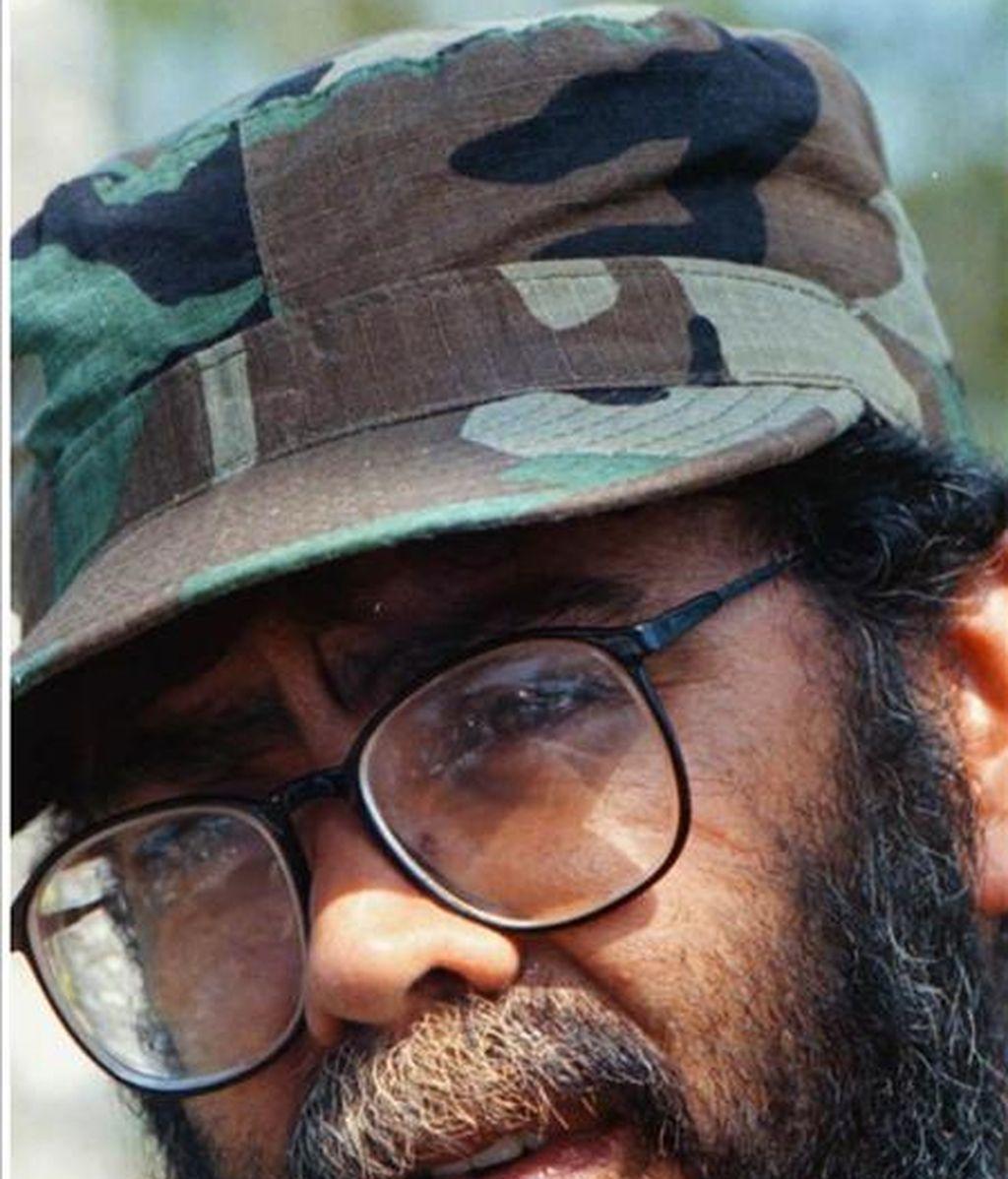 """En el primer vídeo que se da a conocer desde que asumió la jefatura de las FARC, """"Cano"""" aparece de pie, leyendo de un computador portátil un listado de los rehenes canjeables, ante guerrilleros en formación. EFE/Archivo"""