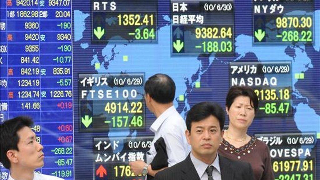 Varias personas pasan por delante de un monitor en el que se muestran las variaciones del índice Nikkei, en Tokio (Japón). EFE/Archivo
