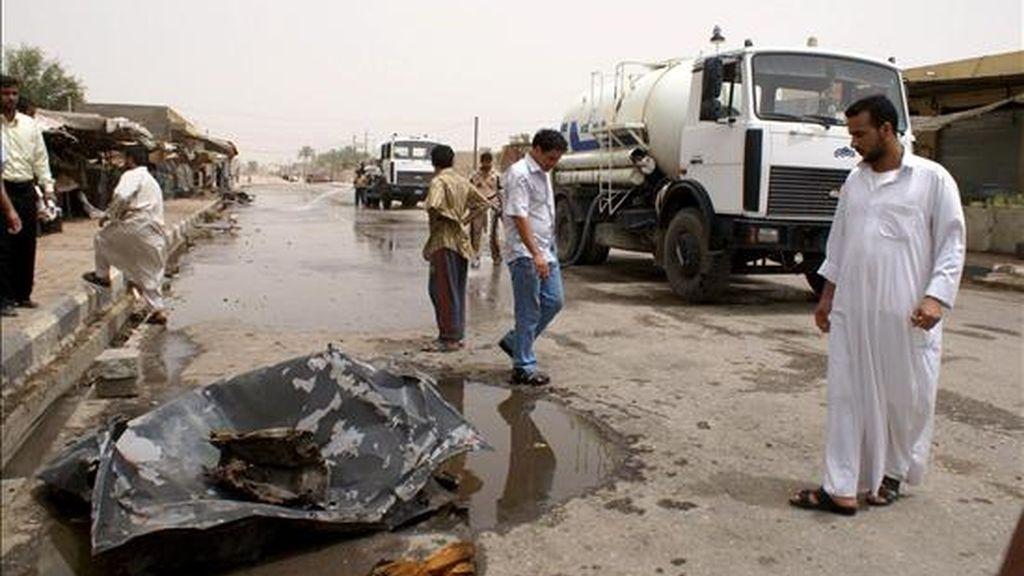 Varios iraquíes inspeccionan los restos de un coche utilizado en un atentado en Nasriya, al sur de Irak hoy miércoles 10 de junio de 2009. Al menos 32 personas han muerto y 47 han resultado heridas tras la explosión de un coche bomba en un mercado de la ciudad sureña iraquí de Nasriya.EFE