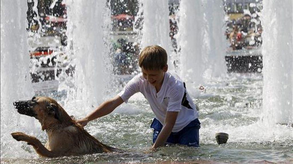 Un niño disfruta refrescándose junto a su perro en una fuente en Podolsk a unos 16 km de Moscú en Rusia el sábado, 17 de julio. Una ola de calor está cubriendo Rusia donde se están alcanzando temperaturas récord de 37 grados. EFE/Archivo