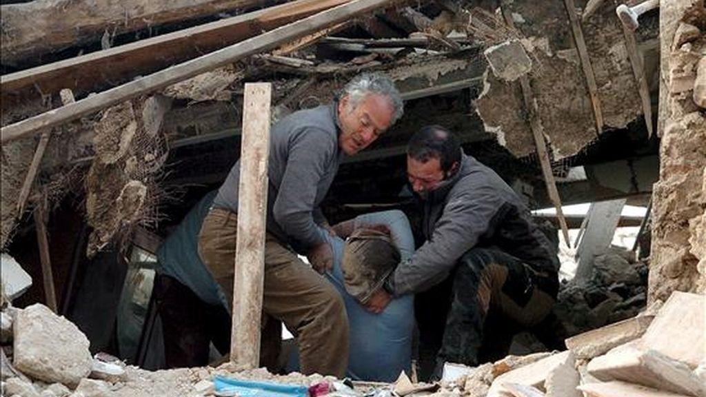 Miembros de los servicios de rescate logran sacar a una mujer herida que quedó atrapada bajo los escombros de su casa tras el seísmo. EFE