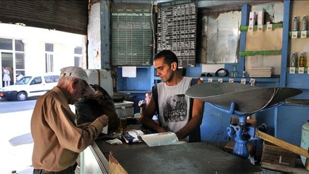 Un bodeguero vende productos racionados a un cliente en La Habana (Cuba). EFE