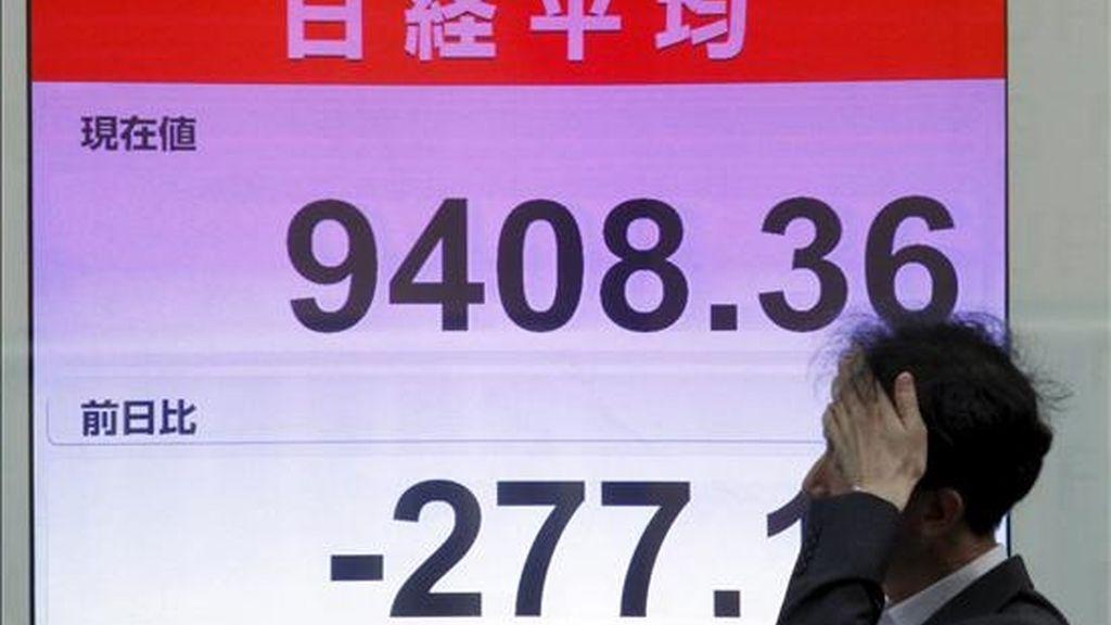 Un empresario pasa junto a una pantalla con los resultados de la Bolsa de Tokio (Japón). EFE/Archivo