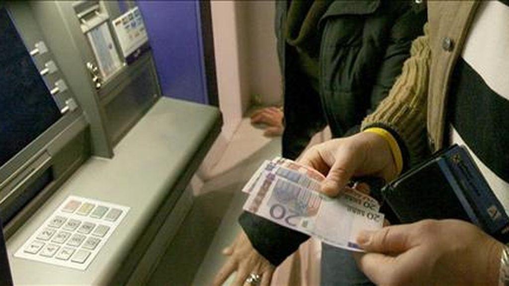 Un hombre observa unos primeros billetes de euros que obtiene de un cajero. EFE/Archivo