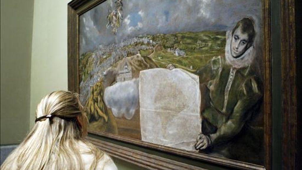 """Una mujer observa el cuadro """"Vista y plano de Toledo"""", de El Greco, procedente del museo dedicado al pintor en la capital castellano-manchega, que ha sido instalado hoy en una de las salas del museo del Prado de Madrid. EFE"""