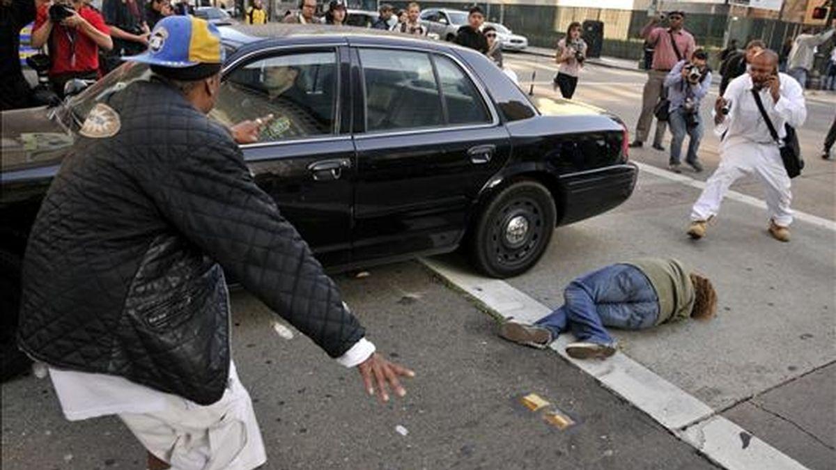 Una manifestante yace en el suelo tras ser arrollada por un carro policial que retrocedía durante una protesta ayer, 8 de julio, en una calle del centro de Oakland, California (EE.UU.) después de que un jurado condenara al ex oficial de tránsito Johannes Mehserle por el homicidio sin premeditación de Oscar Grant en 2009 durante un tiroteo en una plataforma del tren de Oakland. EFE