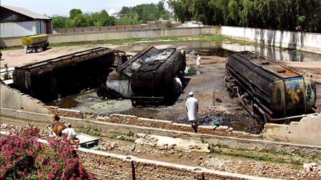 Los trabajadores revisan unos camiones de petróleo de las fuerzas de la OTAN en Afganistán, que fue atacado en Jhagra, Peshawar, Pakistán, hoy, 23 de abril. Las fuerzas estadounidenses y de la OTAN en Afganistán, obtienen un 75 por ciento de sus alimentos y provisiones desde Pakistán.EFE/Arshad Arbab