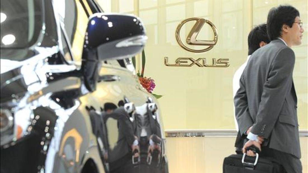 """Un hombre de negocios camina junto a un coche modelo """"Lexus"""" expuesto en uno de los concesionarios de Toyota del centro de Tokio (Japón). EFE/Archivo"""