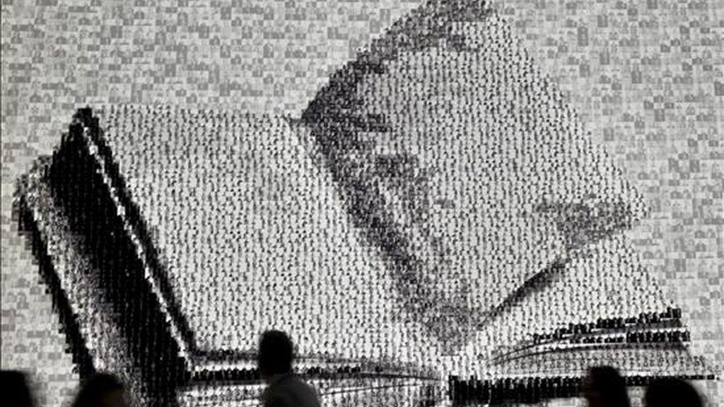 Varios visitantes pasan ante la imagen de un libro a gran escala durante la primera jornada de la Feria del Libro de Fráncfort, hoy en Fráncfort (Alemania). La Feria de Fráncfort, la más grande del mundo en el sector, abrió hoy sus puertas al público, después de su inauguración ayer con Argentina como país invitado de honor. EFE