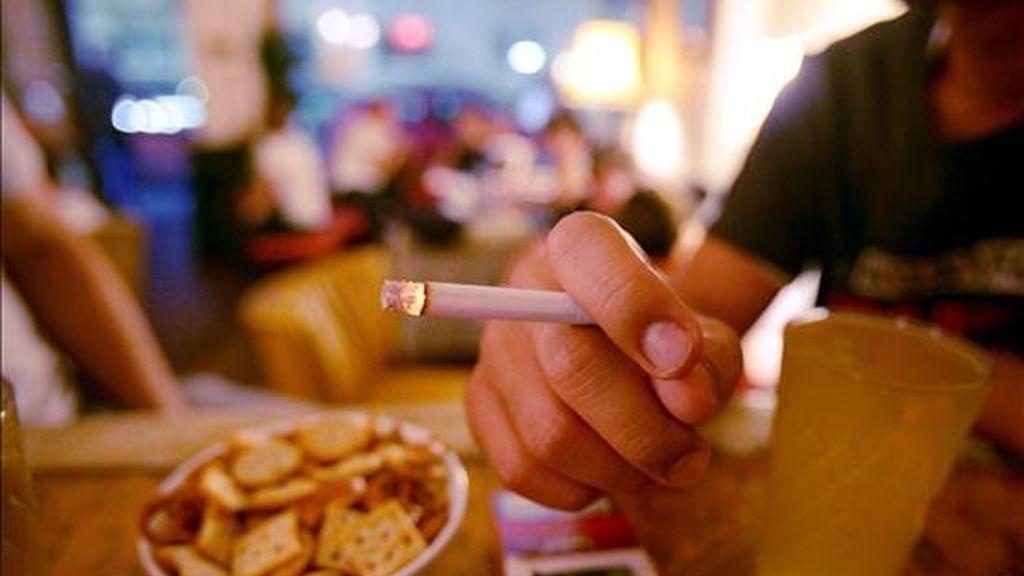 Un hombre fuma un cigarro en un bar. EFE