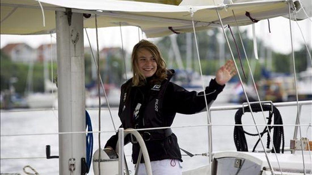 La holandesa Laura Dekker, de 14 años, se despide hoy mientras sale a bordo de su velero del puerto de Den Osse, Zeeland (Holanda). Dekker emprende hoy el viaje en el que espera convertirse en la persona más joven que consigue completar la vuelta al mundo en un barco de vela en solitario. EFE