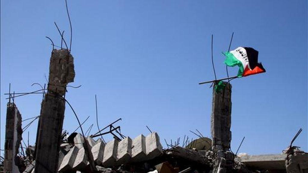 Una bandera palestina ondea en el campo de refugiados de Yabalia sobre las ruinas de una vivienda destruida durante la ofensiva israelí contra Gaza. EFE/Archivo