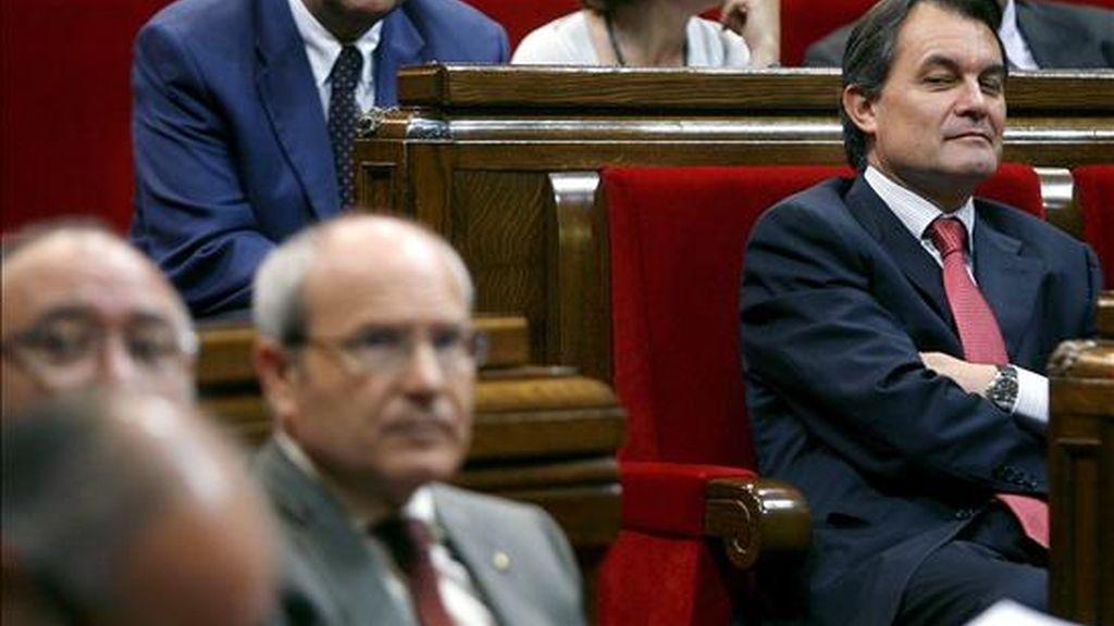 El líder de CiU, Artur Mas (d) mira de reojo al Gobierno catalán, tras la votación del documento que recoge el resultado de los trabajos de la comisión de investigación sobre las irregularidades detectadas en la gestión del Palau de la Música. EFE