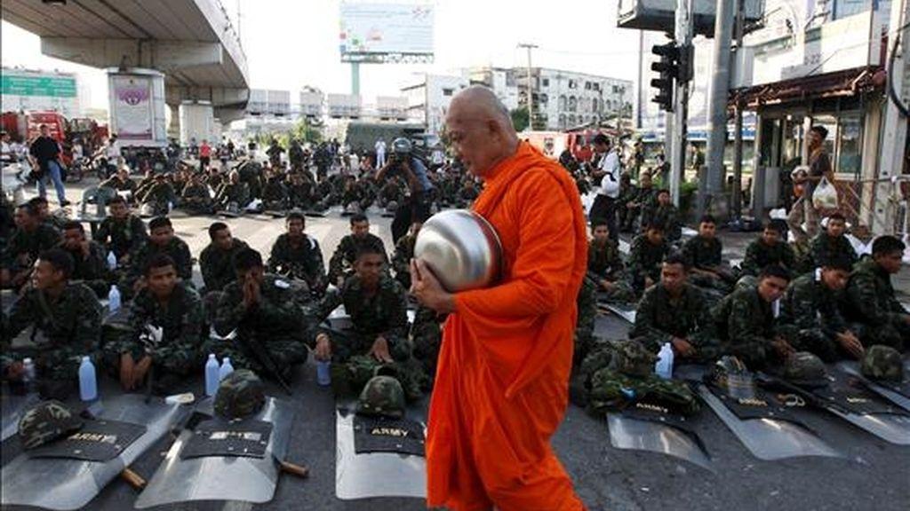 Un monje pasa al frente de varios soldados tailandeses sentados en una de las calles que conduce a la sede del Gobierno en Bangkok. EFE