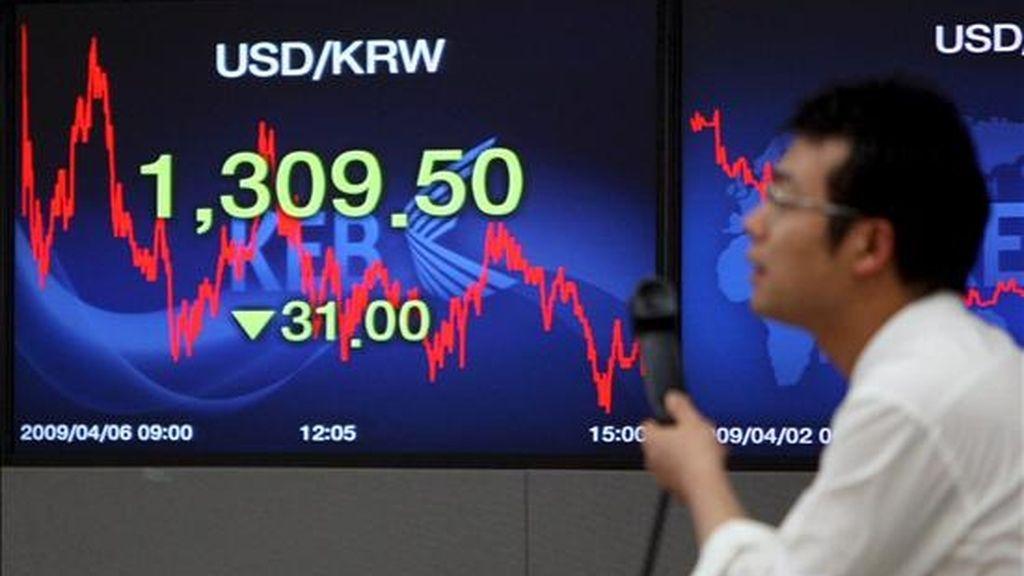 Un hombre pasa por delante de un panel en el que se muestran los valores de la Bolsa, en Seúl. EFE/Archivo