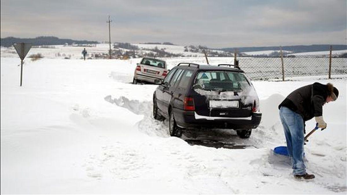Un hombre quita la nieve con una pala para poder sacar su coche, en Rokietnica (Polonia), hoy, 2 de diciembre de 2010. El frío y las intensas nevadas de los últimos días ya se han cobrado la vida de al menos dieciocho personas en Polonia, en su mayoría indigentes. EFE