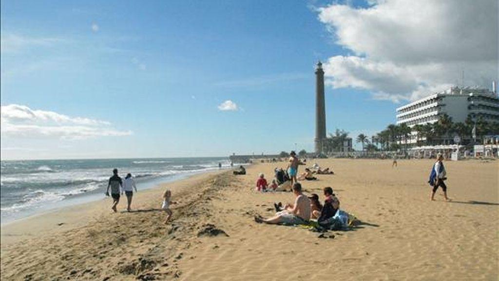 Vista de la playa de Maspalomas, con el faro al fondo, donde los turistas disfrutan del buen tiempo. EFE/Archivo