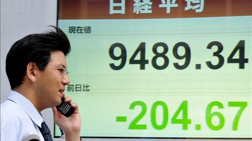 Un empresario japonés que habla por su teléfono móvil pasa junto a un tablero electrónico de la bolsa de valores, en Tokio, Japón. EFE