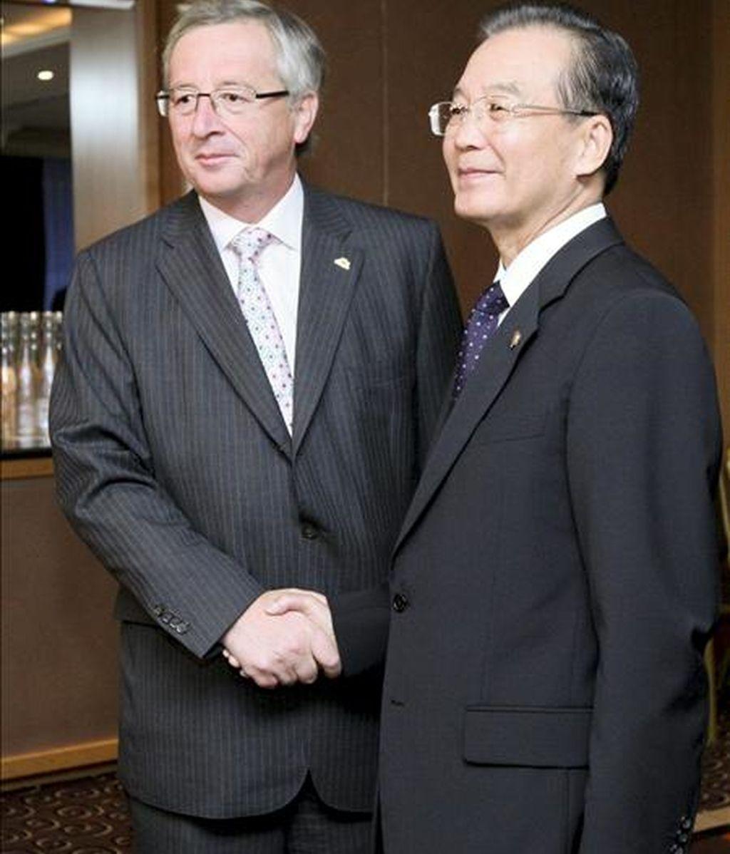 """El primer ministro chino, Wen Jiabao (dcha), saluda a su homólogo luxemburgués, Jean-Claude Juncker, presidente del Eurogrupo, durante la reunión financiera de la """"troika"""" celebrada hoy, martes, 5 de octubre de 2010 en el ámbito de la cumbre de líderes de Europa y Asia (ASEM) en Bruselas (Bélgica). Los jefes de Estado y Gobierno de más de 40 países de Europa, Asia y Oceanía debaten hoy la coordinación de sus políticas para afianzar la recuperación económica global, sobre la que aún pesan incertidumbres. EFE"""