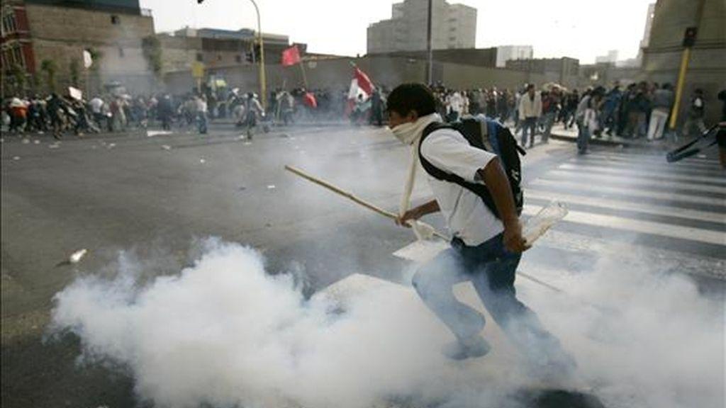 Un estudiante escapa de los gases lacrimógenos lanzados por la policía durante una multitudinaria marcha que pretendía llegar al Congreso, en el centro de Lima, en solidaridad con los pueblos amazónicos que reclaman la derogatoria de un paquete de leyes. EFE