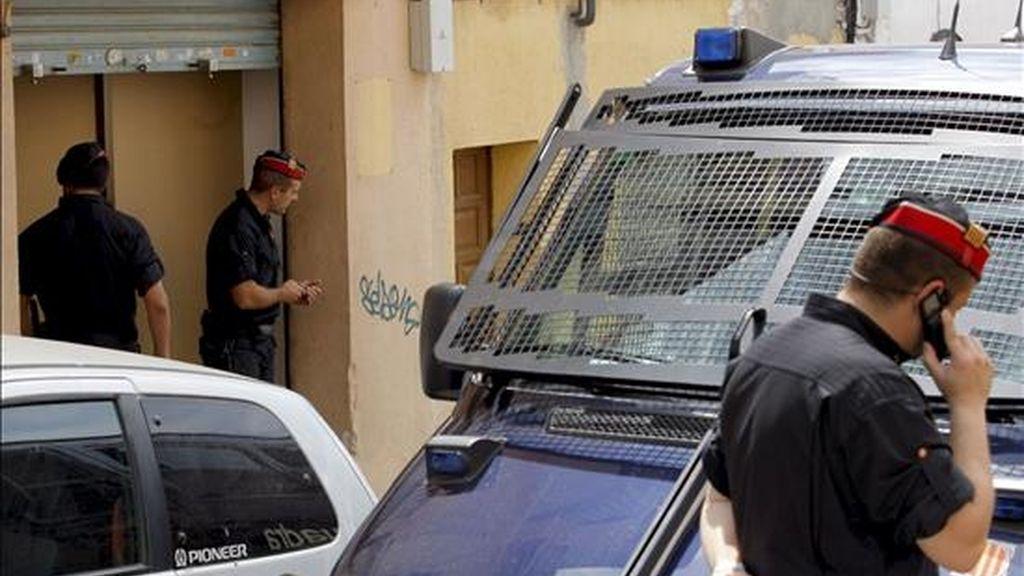 Agentes de los Mossos d'Esquadra vigilan la entrada de uno de los locales registrados durante la operación en la que se inspeccionaron unos 70 talleres clandestinos textiles regentados por ciudadanos de origen chino en Mataró (Barcelona). EFE/Archivo