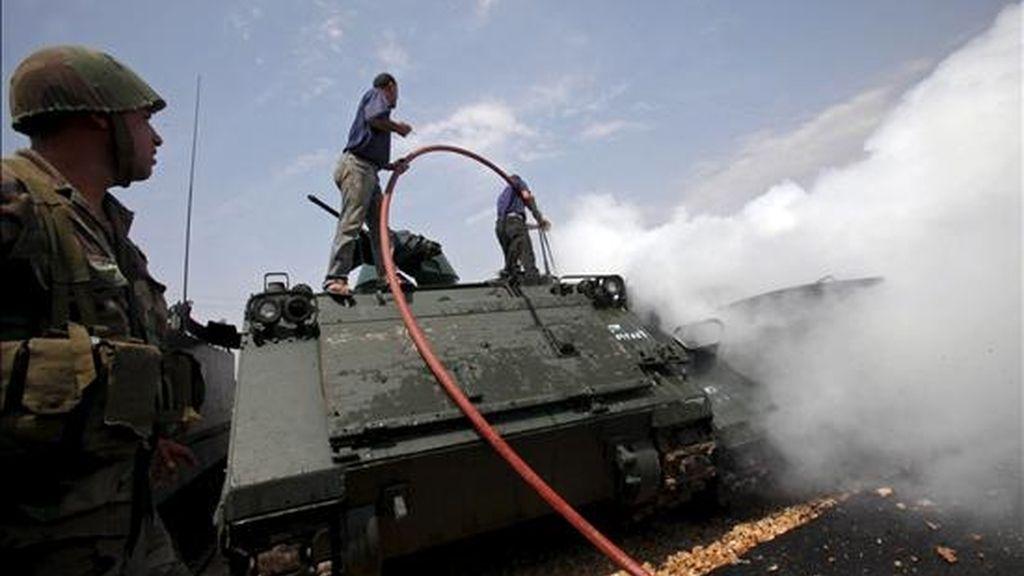 Varias personas apagando el incendio de un vehículo acorazado del Ejército libanés en la base militar de Taibeh, en el Líbano, este martes. EFE