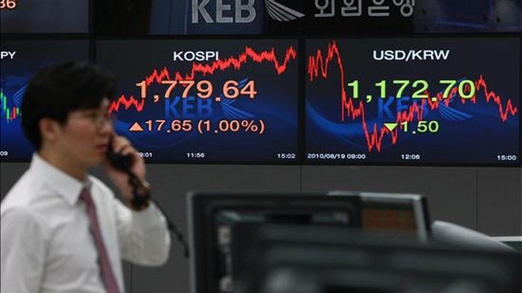 Un agente habla por teléfono frente a una pantalla en la que se reflejan los datos de los parqués internacionales, en la Bolsa de Seúl . EFE/Archivo