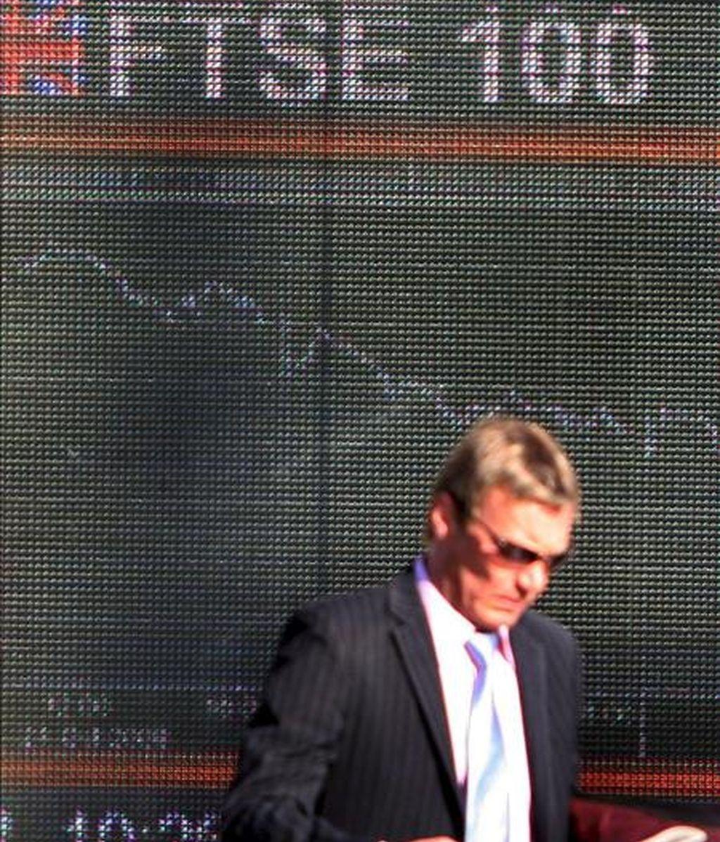 Un hombre pasa por delante de un panel electrónico que muestra el valor de la Bolsa de Londres. EFE/Archivo