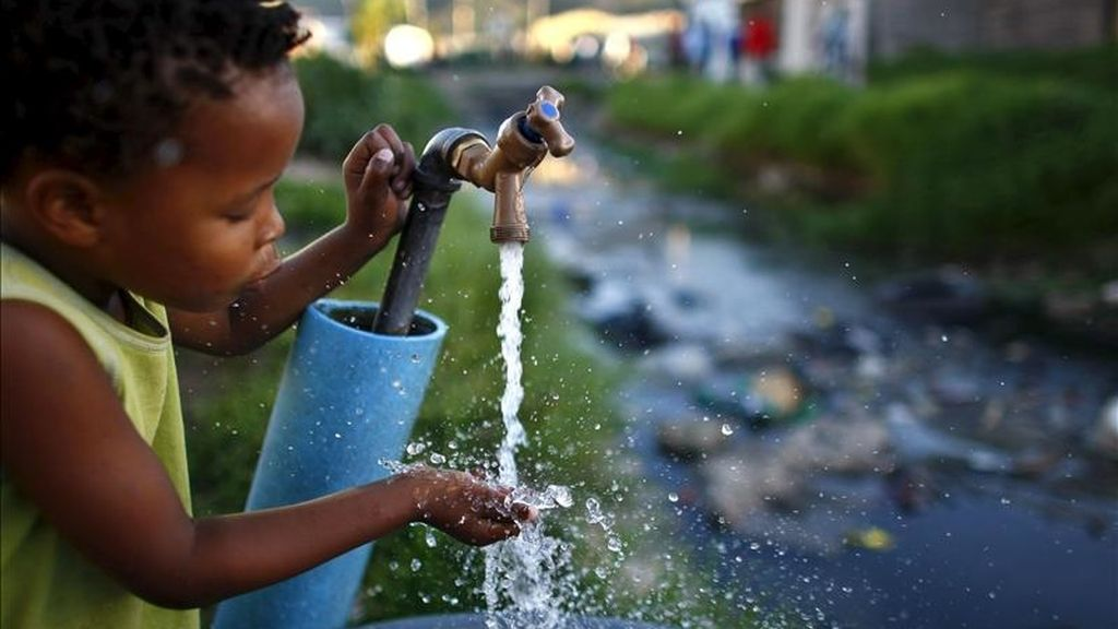 Un niño sudafricano bebe agua de una fuente situada junto a un río contaminado en el asentamiento de Masiphumelele, en Ciudad del Cabo (Sudáfrica). EFE/Archivo