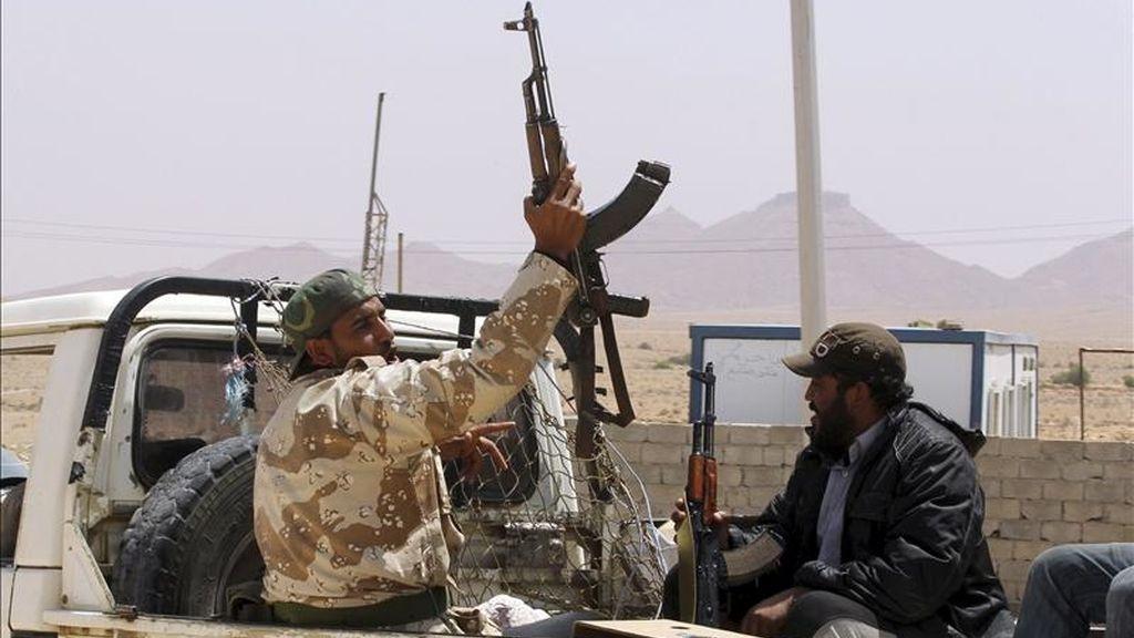 Un rebelde libio alza su rifle en la parte trasera de una camioneta en la parte libia del paso fronterizo de Wazin, en el lado sur de la frontera con Túnez, en Libia. EFE