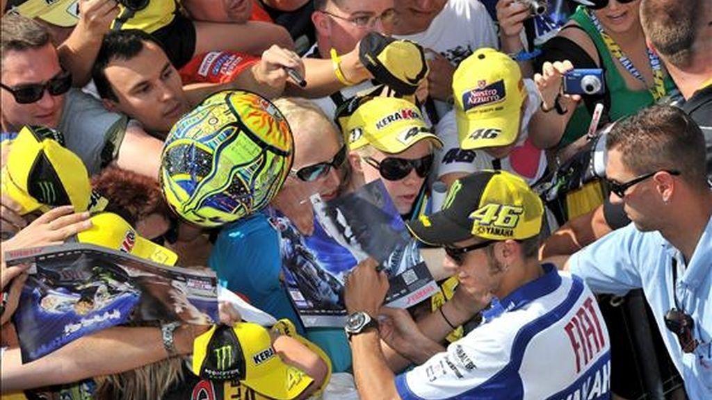 El italiano Valentino Rossi (2-d) firma autógrafos a sus fans en el circuito Sachsenring en Hohenstein-Ernstthal, donde este domigo se disputa el Gran Premio de Alemania, hoy, viernes, 16 de julio de 2010. EFE