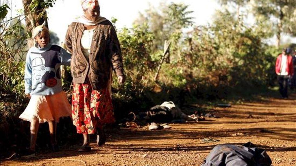 Residentes de Gathaithi pasan delante de los cadáveres de sus familiares y vecinos asesinados por miembros de la secta ilegal Mungiki. EFE